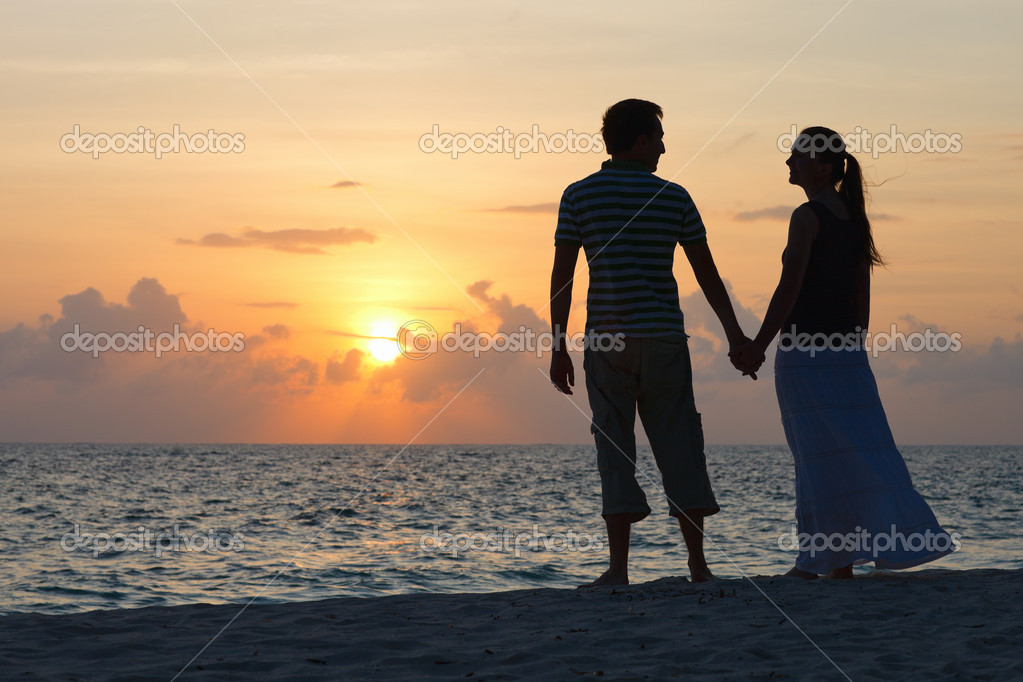 Silhouettes of romantic couple on tropical beach at sunset — Stock Photo #4046011