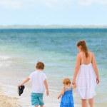 Family walking along tropical beach — Stock Photo #4093565