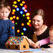 Family making gingerbread house - Stock Photo