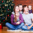 Family near Christmas tree - Stock Photo