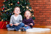 Brother and sister near Christmas tree — Stock Photo