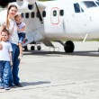 Mother and kids in front of airplane — Stock Photo