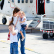 Mother and kids in front of airplane - Stock Photo