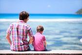 Отец и сын, сидя на берегу океана — Стоковое фото