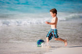 Menino brincando com bola na praia — Fotografia Stock