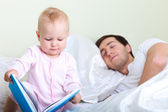 Baby reading to father — Stock Photo