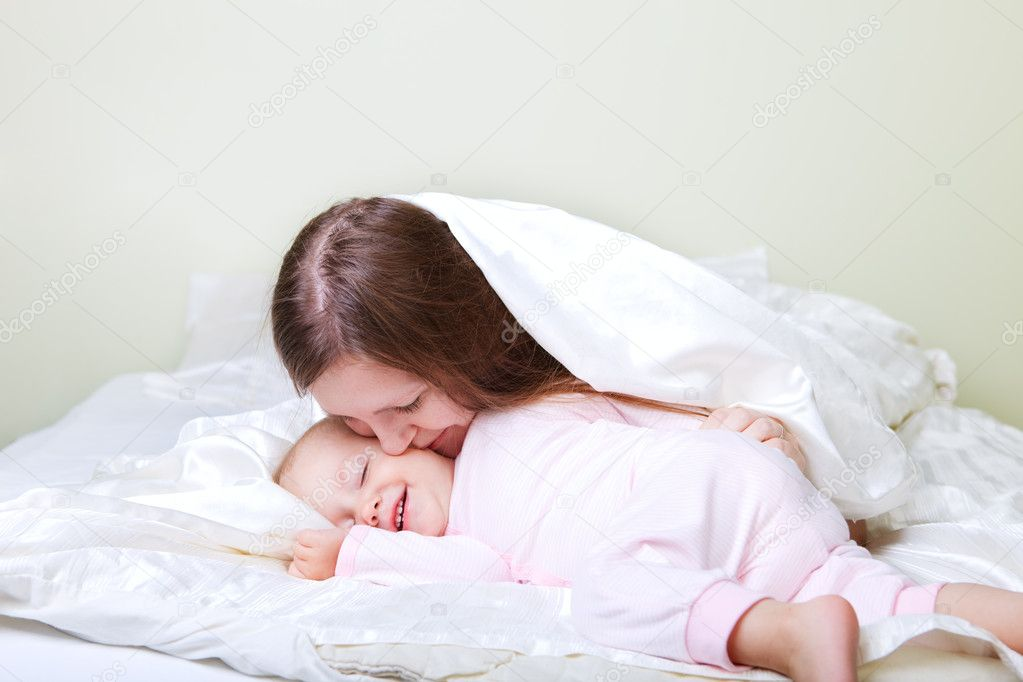 Young mother and baby girl playing in bed — Stock Photo #4729542