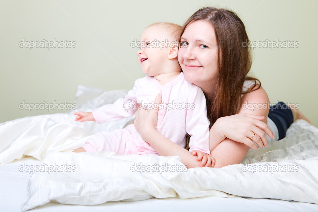 Beautiful young mother with her baby daughter in bedroom  Stock Photo #4729545