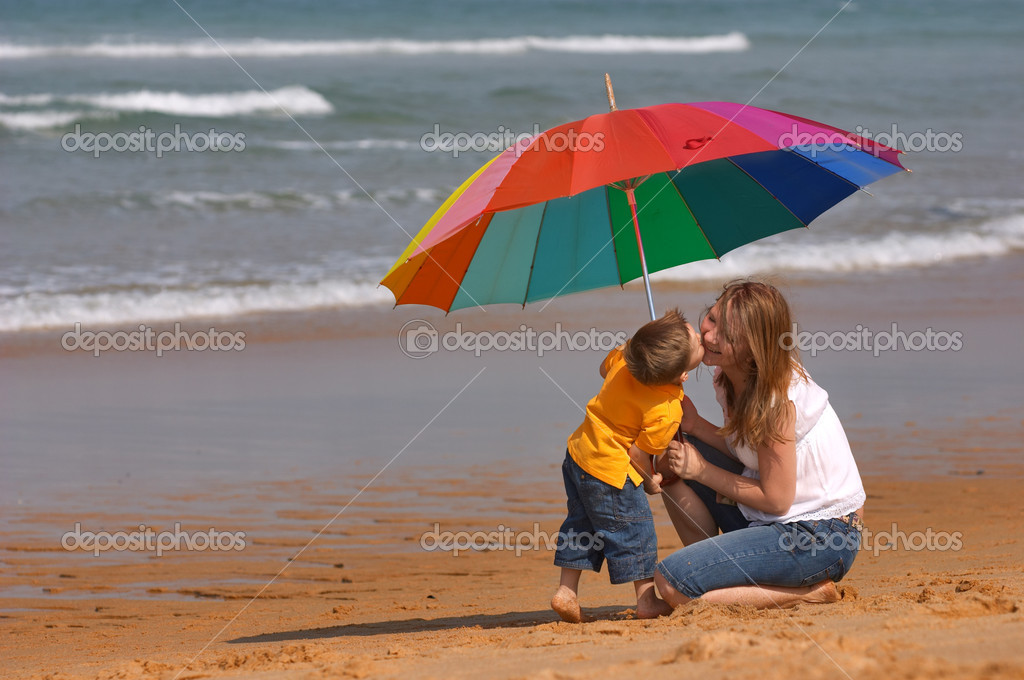 Do not depend on weather conditions. Happy young woman and kid under brightly colored umbrella having fun outdoors. — Stock Photo #4729668