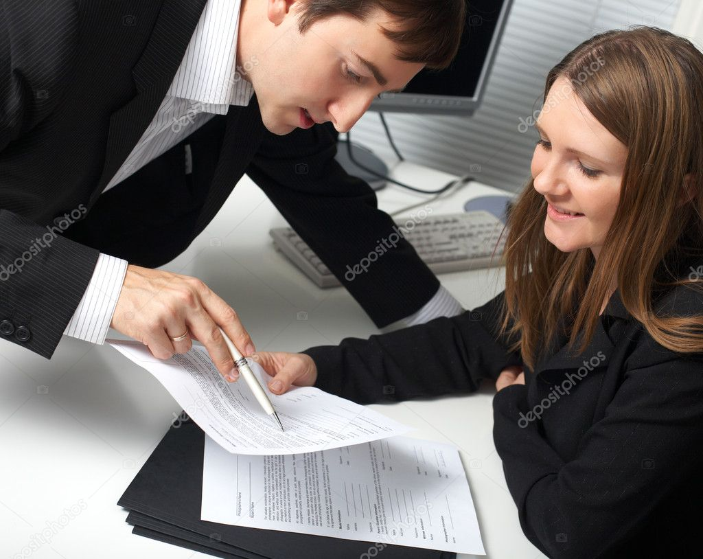 Two contemporary businesspeople discussing a document — Stock Photo #4729902