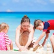 Mother with kids on beach vacation — Stock Photo