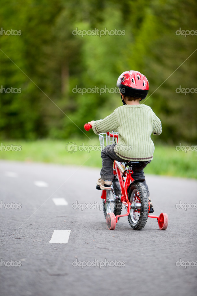 3 years old boy wearing safety bicycle helmet riding a bike — Stock Photo #4730505