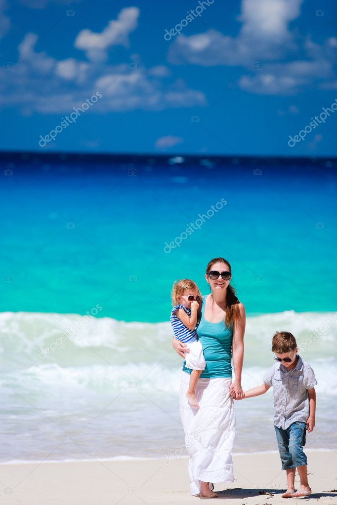 Family walking along beautiful tropical beach at Seychelles  Stock Photo #4748373