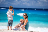 Mother with kids on tropical beach — Stock Photo