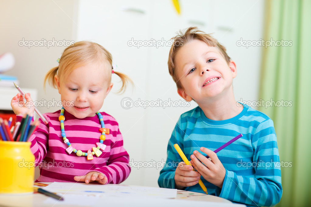 Portrait of two small kids drawing with coloring pencils  Stock Photo #4872971