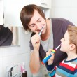 Stock Photo: Father and son brushing teeth