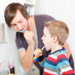 Father and son brushing teeth — Stock Photo