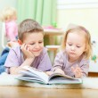 Brother and sister reading - Stock Photo