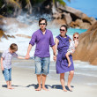 Young family walking along beach — Stock Photo #5215210