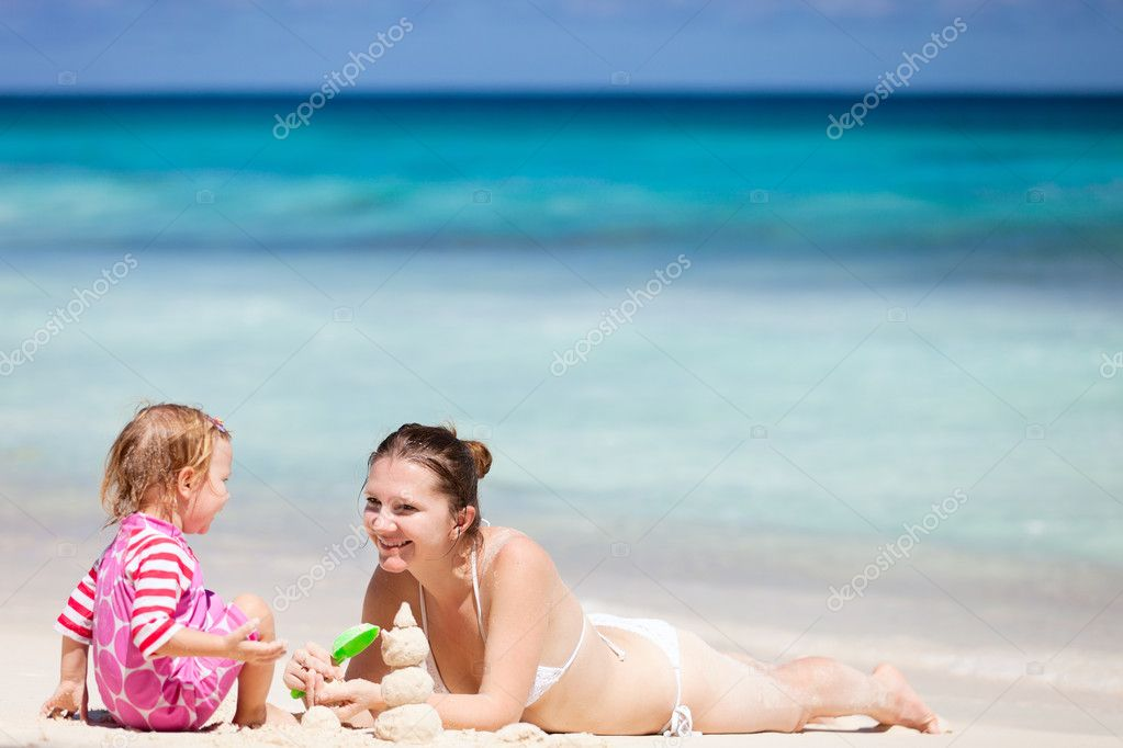 Mother and daughter playing with sand at tropical beach — Stock Photo #5215556