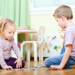 Brother and sister solving puzzle - Stock Photo