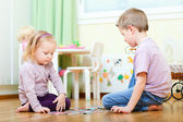 Brother and sister solving puzzle — Stock Photo