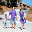 Young family walking along beach - Stock Photo