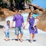 Young family walking along beach — Stock Photo