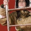 Stock Photo: Girl in fireman uniform upstairs