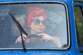 Vintage girl in car under rain — Stock Photo