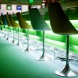Chairs in bar with green lights - Stock Photo