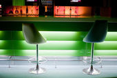 Chairs in row in bar with bottles with green lights — Stock Photo