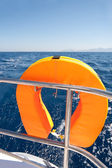 Orange lifebuoy on sailing ship — Stockfoto