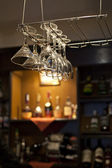 Wine glasses hanging near bar counter — Stock Photo