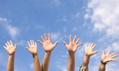 Hands rised up in air across sky — Foto Stock
