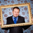 Businessman in golden frame on wallpapers — Stock Photo