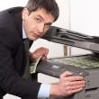 Businessman make false money on copy machine - Stock Photo