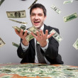 Businessman in office catch money in the air — Stock Photo