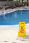 Caution wet floor near pool — Stock Photo