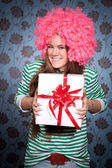 Girl in pink wig with gift — Stock Photo