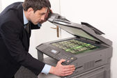 Businessman make false money on copy machine — Stock Photo