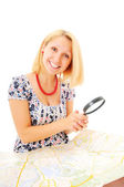 Beautiful young smiling girl with magnifying glass and map — Stok fotoğraf