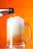 Pouring beer over orange background — Stock Photo