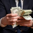 Businessman counts money in hands. — Stock Photo #5029369