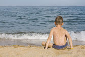 De jongen zit op water — Stockfoto