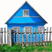 Vieille clôture en bois contre le bâtiment bleu — Photo