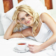 Portrait of beautiful young woman with cup on bed — Stock Photo
