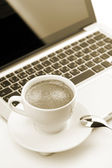 Cappuccino cup on laptop — Stockfoto