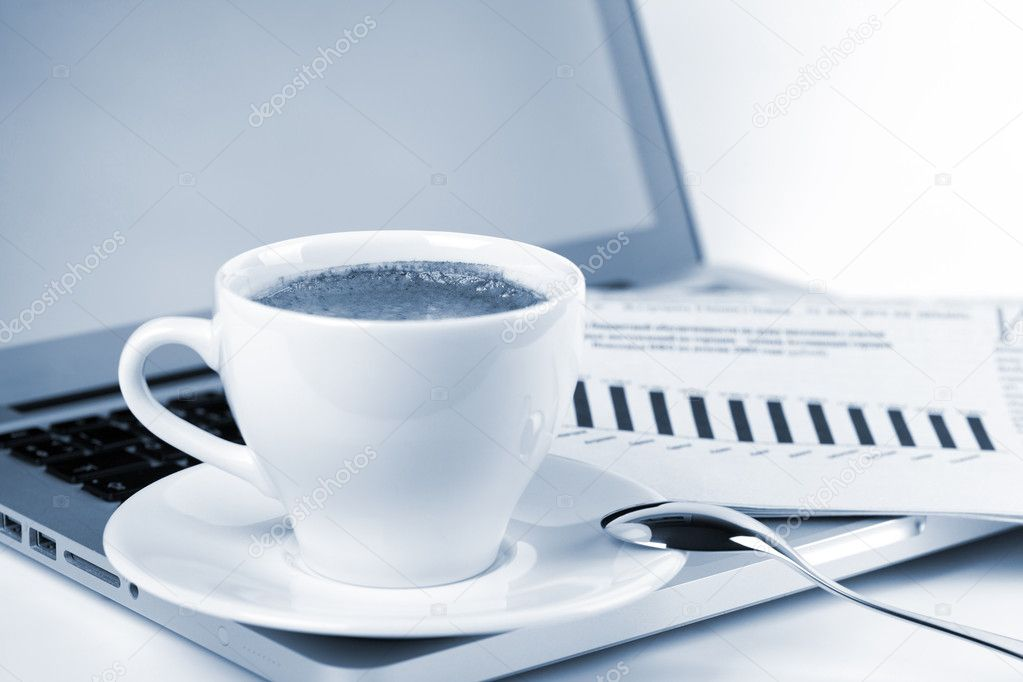 Cappuccino cup with laptop and newspaper. Blue toned — Stock Photo #4633985