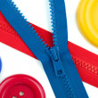 Three colored sewing buttons and two zippers closeup — Stock Photo